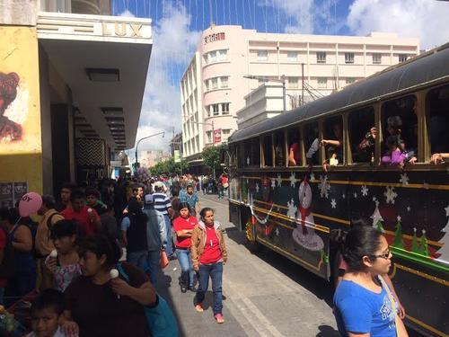 Cientos de guatemaltecos recorren a pie la sexta avenida de la zona 1 capitalina, mientras otros lo hacen en el tren navideño. (Luis Barrios/Soy502)