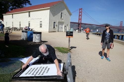 Un trabajador, Michael Faw, del Servicio Nacional de Parques, coloca un cartel que anuncia el cierre del centro de servicio en el parque Crissy Field en San Francisco, California.