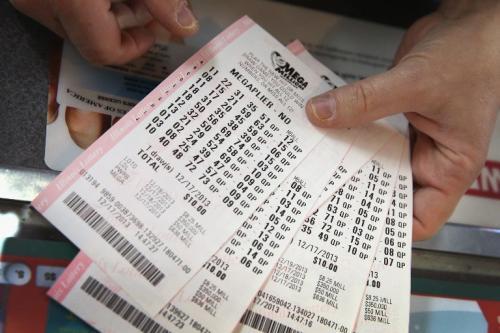 Un cliente muestra unos billetes de la lotería Mega Millions. El premio mayor es actualmente el segundo más grande en la historia de EE.UU. (AFP)