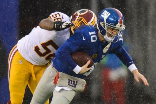 Eli Manning es derribado en una acción del juego contra los Redskins de Washington. (AFP)