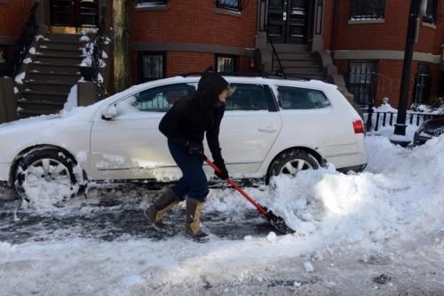 Una mujer quita la nieve de su carro con una pala en Concord Street East, Massachusetts. La tormenta comenzó a mediodía el jueves con fuertes nevadas durante la noche hasta el viernes. (AFP)