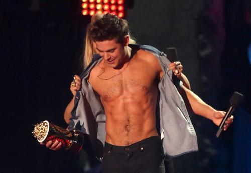 El actor Zac Efron mostró su trabajado torso para aceptar el premio a la Mejor actuación sin camisa en los MTV Movie Awards 2014. (Foto: Christopher Polk/AFP)