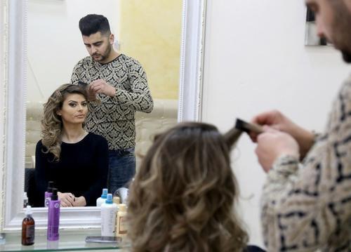 Greta Hoxhaj se prepara para entrar al set donde presenta las noticias con ropa ligera. (Foto: AFP)