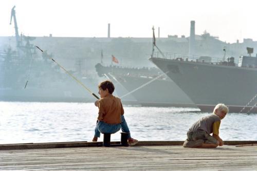 Niños ucranianos juegan en el puerto de Sebastopol frente a los botes rusos. (Foto: AFP)