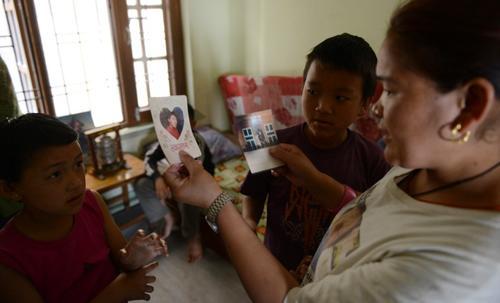 Las familias de los Sherpas piden una indemnización equivalente a los US$10 mil.  En esta foto los familiares de Tenzing Chottar Sherpa, desaparecido en la la avalancha del Monte Everest sostienen su fotografía en Katmandú, Nepal.  (Foto: AFP)