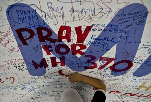 Un empleado de Malasyia Airlines, escribe un mensaje buenos deseos para los pasajeros del vuelo MH370. (Foto:AFP)