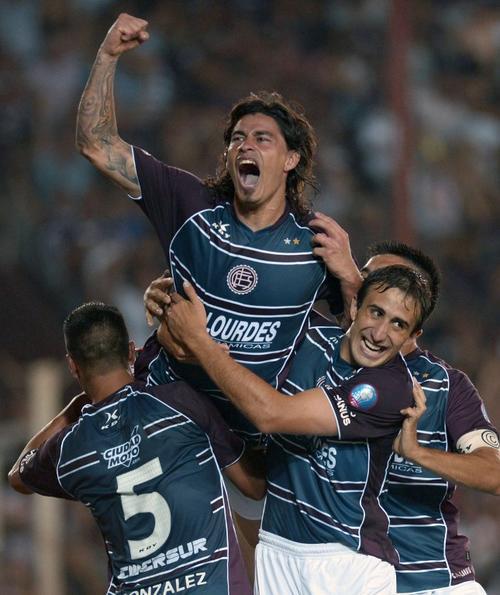 Ismael Blanco de Lanus celebra con todo junto a sus compañeros, Diego Gonzalez (5)  y Carlos Izquierdoz, en el gol del cuadro argentino. (AFP)
