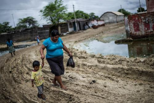 Una mujer y su hijo pasan en medio del lodo que se formó en su comunidad luego de las inundaciones por las intensas lluvias. (Foto: AFP)