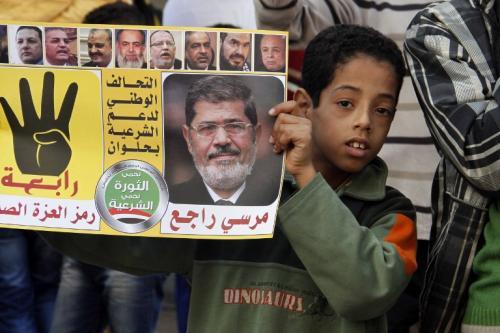 Un niño porta un cartel con la foto del ex presidente Mohamed Mursi, como muestra de protesta contra el actual gobierno. (Foto: AFP)