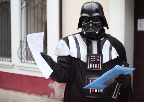 Un ucraniano vestido como Darth Vader muestra documentos de su candidatura fuera del ayuntamiento de la ciudad del sur de Ucrania. (Foto AFP)