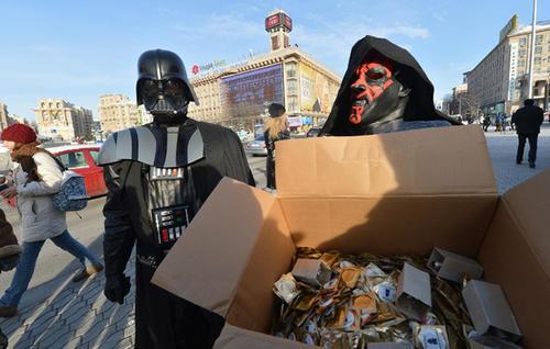 Un dirigente del Partido de Internet de Ucrania, vistiendo un traje de Darth Vader de la saga de Star Wars, así como un activista distribuyen  productos a los ciudadanos en la Plaza de la Independencia en Kiev. (Foto: AFP)
