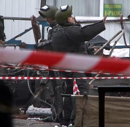Dos expertos en demolición rusos que llevan un equipo especial de trabajo cerca de los restos del trolebús. (AFP)