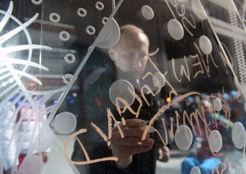 Vladimir Putín firma el muro de visitantes de la Villa Olímpica. (Foto: AFP)