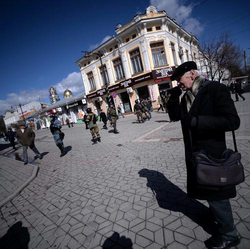 Un hombre camina frente al Parlamento de Crimea en medio de soldados milicianos. Crimea declaró su independencia y solicitó este lunes su adhesión a Rusia. (Foto:AFP)