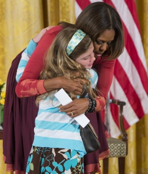Michell Obama tomó el currículum entregado por la niña. (Foto:AFP)