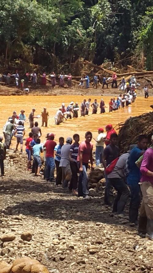 Un grupo de personas afectadas y miembros del CONAP formaron una cadena humana para transportar víveres. (Foto: CONAP)