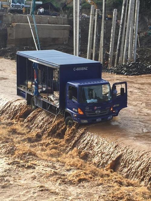 El piloto del camión abandona el vehículo para ser rescatado de la crecida del río Tinoco, en El Estor. (Foto: Conred)
