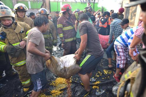 En una cadena humana, los vendedores del mercado La Terminal, sacan los productos que no fueron consumidos por el fuego. La angustia se vive de nuevo. (Foto: Jesús Alfonso/Soy502)