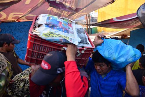 Vendedores ponen a salvo del fuego sus productos. (Foto: Jesús Alfonso/Soy502)