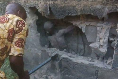 El pequeño permanece inmóvil mientras un rescatista rompe la pared para rescatarlo. (Foto: Channels TV)