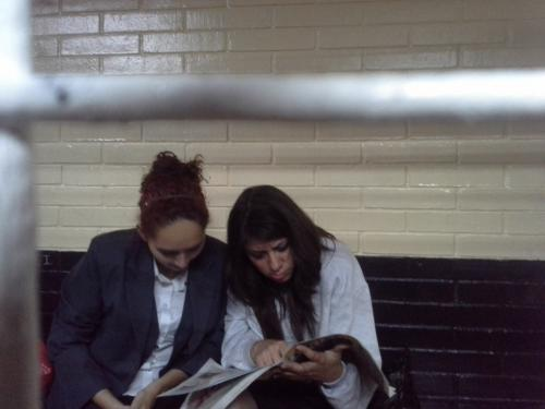 Cristal e Yvette las dos responsables del ataque a la vicepresidente leen los diarios mientras esperan su turno para declarar. Foto Jesús Alfonso/Soy502