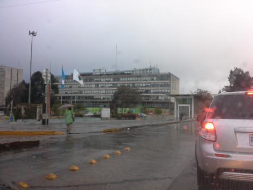 En el Centro Cívico una mujer se cubre de la lluvia.