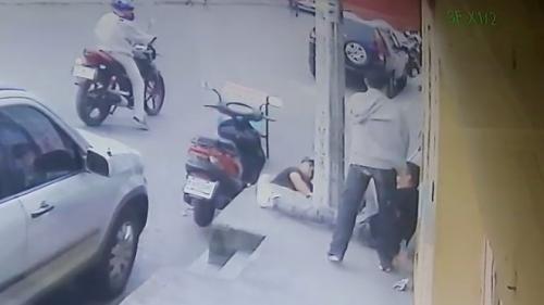 En la imagen se observa que el hombre de sudadero gris le disparó al joven, quien se encontraba sentado en la banqueta en la 17 avenida y 8.ª calle de la zona 14. (Foto: captura de pantalla)