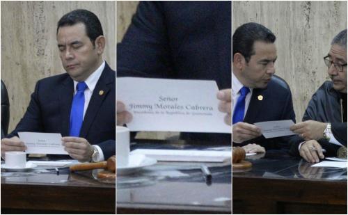 El presidente Jimmy Morales parece que encontró un mensaje en su identificador de mesa, lo observa y lo muestra al presidente de la CSJ, José Pineda. (Fotos: Wilder López/Soy502).