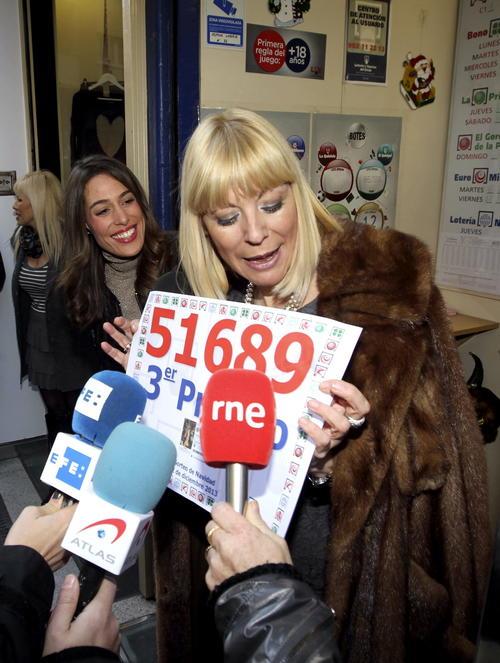 Yolanda Delgado, propietaria de la administración de Lotería 22 de Zaragoza, muestra un cartel con el número 51.689, correspondiente al tercer premio del Sorteo de Navidad, del que ha vendido treinta series, por lo que ha repartido 15 millones de euros. (Foto: EFE/Javier Cebollada)