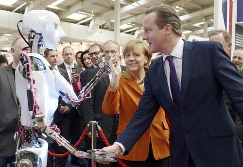 La canciller alemana Angela Merkel y el primer ministro británico David Cameron observando un robot en la feria CeBIT 2014 en Hannover, Alemania. (Foto: EFE/Rainer Jensen/Deutsche Messe)