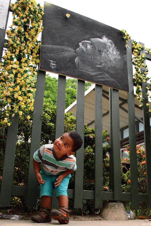 Un pequeño observa la fotografía de Gabriel García Márquez que ha sido colocada afuera de su casa. (Foto: EFE)