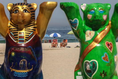 Dos personas toman el sol frente a dos esculturas  en la playa Leme en Río de Janeiro. (Foto: EFE/Antonio Lacerda)