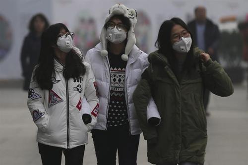 Mujeres caminan por una calle de Pekín en medio de una fuerte niebla causada por la contaminación. (Foto EFE)