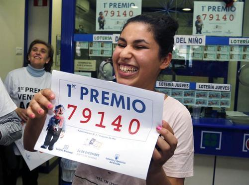 Una joven celebra que lleva un décimo del número 79.140, agraciado con el Gordo de Navidad del Sorteo Extraordinario de la Lotería celebrado hoy y vendido íntegramente. (Foto: EFE)