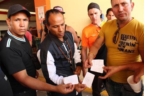 Tres cubanos muestran un documento que certifica que fueron atendidos en un centro de salud del país en diciembre en la ciudad de David, Chiriquí (Panamá). (Foto: EFE)