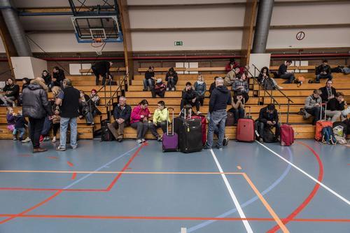 Varios pasajeros descansan en un polideportivo en Zaventem, cerca de Bruselas. (Foto: EFE)