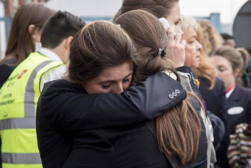 Dos trabajadoras del aeropuerto se abrazan mientras son evacuadas junto a los pasajeros de la zona. (Foto: EFE)