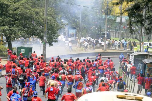 Aficionados rojos persiguen a los Cremas, en las afueras del estadio Manuel Carrera de El Trébol. (Foto: Nuestro Diario)
