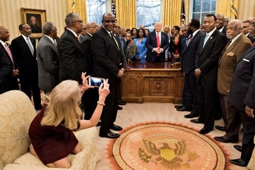 La asesora de Donald Trump toma una extraña postura para tener un mejor ángulo en la fotografía que tomó. (Foto: AFP)