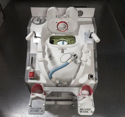 Este modelo de inodoro espacial permite atarse los pies con una correa para no salir flotando. (Foto: Gizmodo)