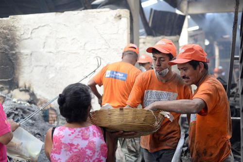 Muestras de solidaridad: Mujeres repartían sandía a los trabajadores que llevan a cabo la labor de retirar los escombros en el mercado La Terminal. (Foto: Esteban Biba/Soy502)
