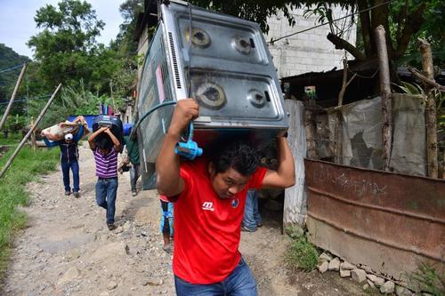 Los vecinos de El Cambray sacan las pocas pertenencias que tienen del barranco. El ambiente en la comunidad es de enorme tristeza. (Foto: Jesús Alfonso/Soy502)