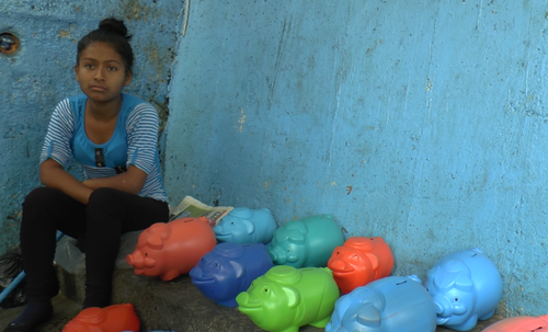 """La hermana de las fallecidas vende """"cochitos"""" en las gradas de acceso al mercado. (Foto: Jesús Alfonso/Soy502)"""