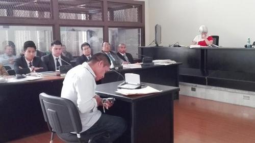 El investigador Reginaldo Coc verifica arma decomisada durante la captura de uno de los sicarios (Foto Marcia Zavala/Soy502)