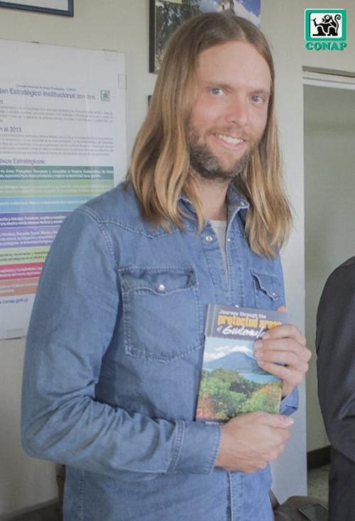 El guitarrista de Maroon 5, James Valentine, muestra un libro sobre las áreas protegidas en Guatemala. (Foto Conap)