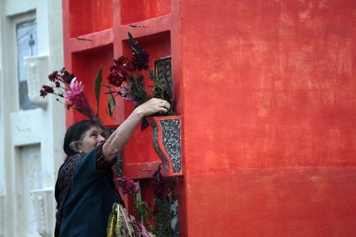 Los familiares limpian y adornan las tumbas de los muertos para celebrar un gran día. (Esteban Biba/EFE)