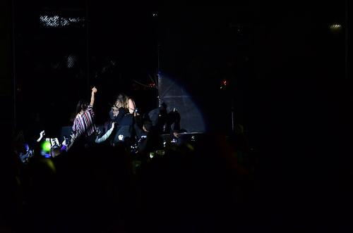 Dos fanáticas comparten el escenario con Enrique Iglesias, quien recuesta su cabeza en una de ellas. (Foto: Selene Mejía/Soy502)
