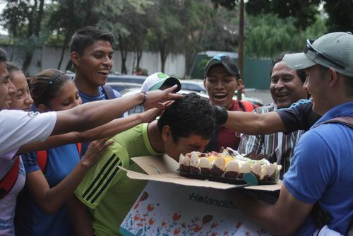 Dos años después de que Erick Barrondo obtuviera la primera medalla Olímpica del país, festeja de forma sencilla mordiendo un pastel que sus compañeros de selección le obsequiaron. (Foto: Luis Barrios/Soy502)