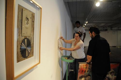 Los curadores examinan detalles en el montaje de la piezas.