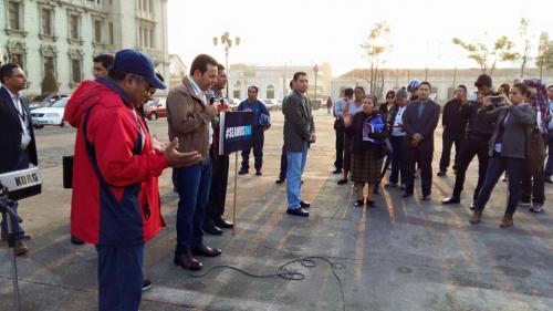 Rodeado de su equipo de seguridad, el presidente Jimmy Morales oró frente al Palacio Nacional de la Cultura. (Foto: Presidencia)
